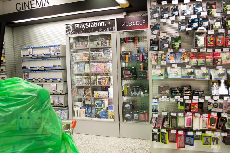 閉店直前のコンビニのような業態の店舗。左側の映画コーナーは壊滅していますが、ゲームはあまり売れていない模様です。棚にはPlayStation とありますが、Xbox 360 パッケージの放つエメラルド色の輝きもみられます。右手はゲームとスマートフォンのアクセサリ。