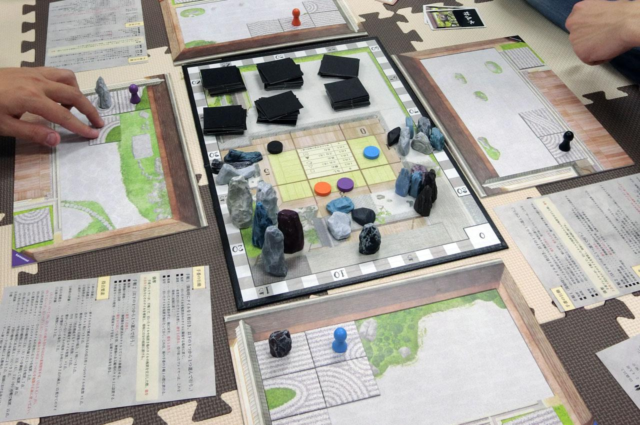 ボードゲーム『枯山水』はルールの共同処理をゲームに組み込んだ秀逸な内容だ。他プレイヤーを手伝うことで、ゲーム中の平均通貨があがり、美しい庭ができる。また、ゲーム終了時の勝利点計算の手法は、プレイヤーが枯山水の出来映えを確認し合うことで「感想戦」を内包する。