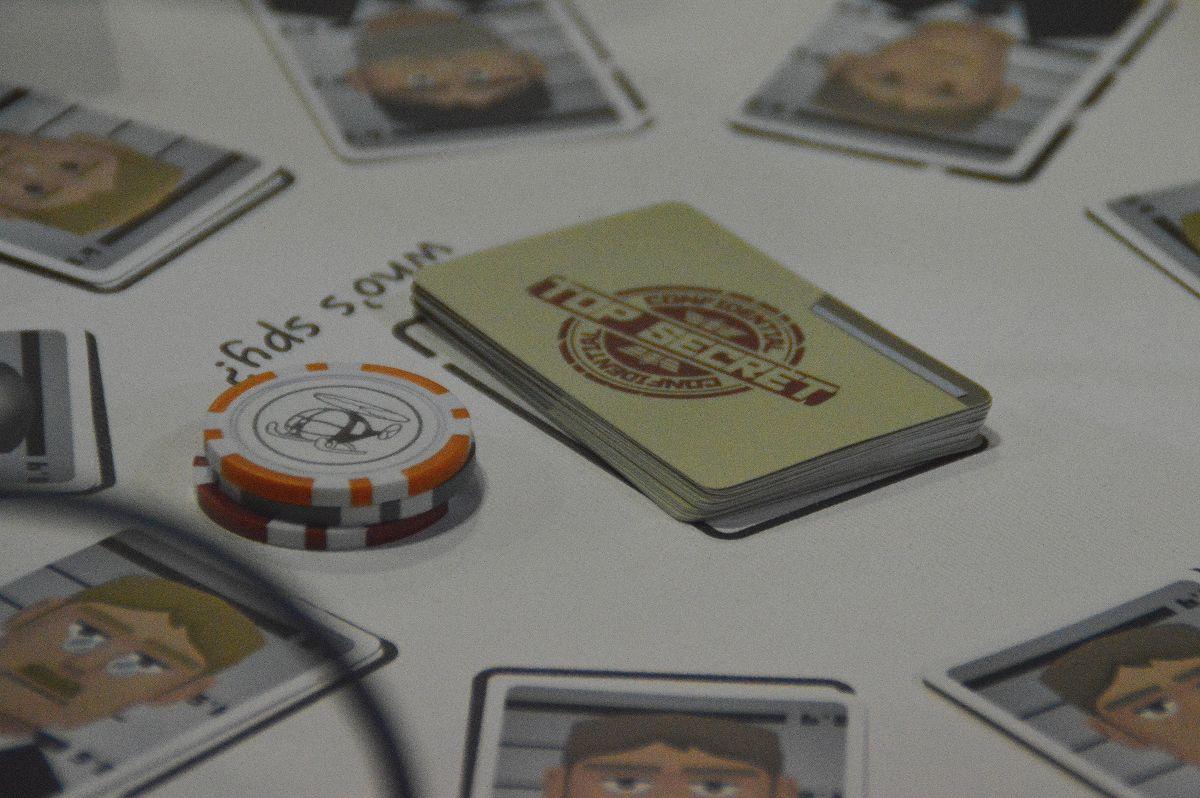 テーブル中央に並べられた手配書カード。ちなみにもし誰かが手配書カードを引いたら、中央の山札から補充していくようになっている。左側に積まれているのは手配書を揃えた先着順で入手する「脱出手段トークン」。最終スコアに関わる